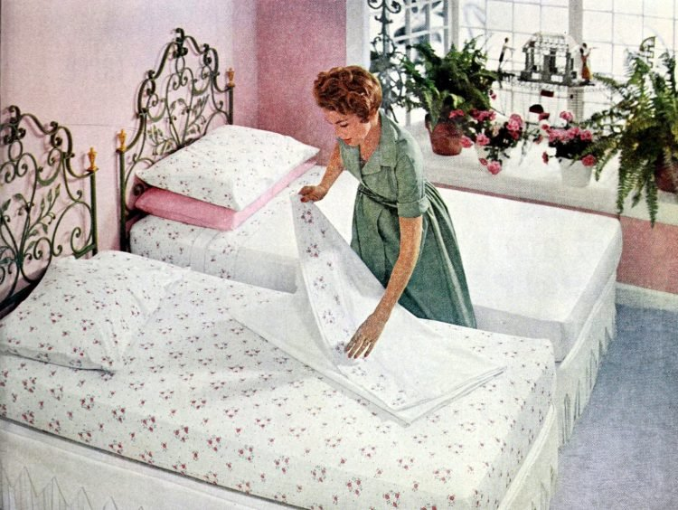 1950s woman changing sheets on twin beds