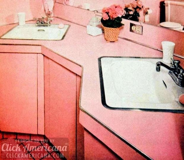 Retro pink bathrooms: White sinks, inset in pale pink angled cabinetry