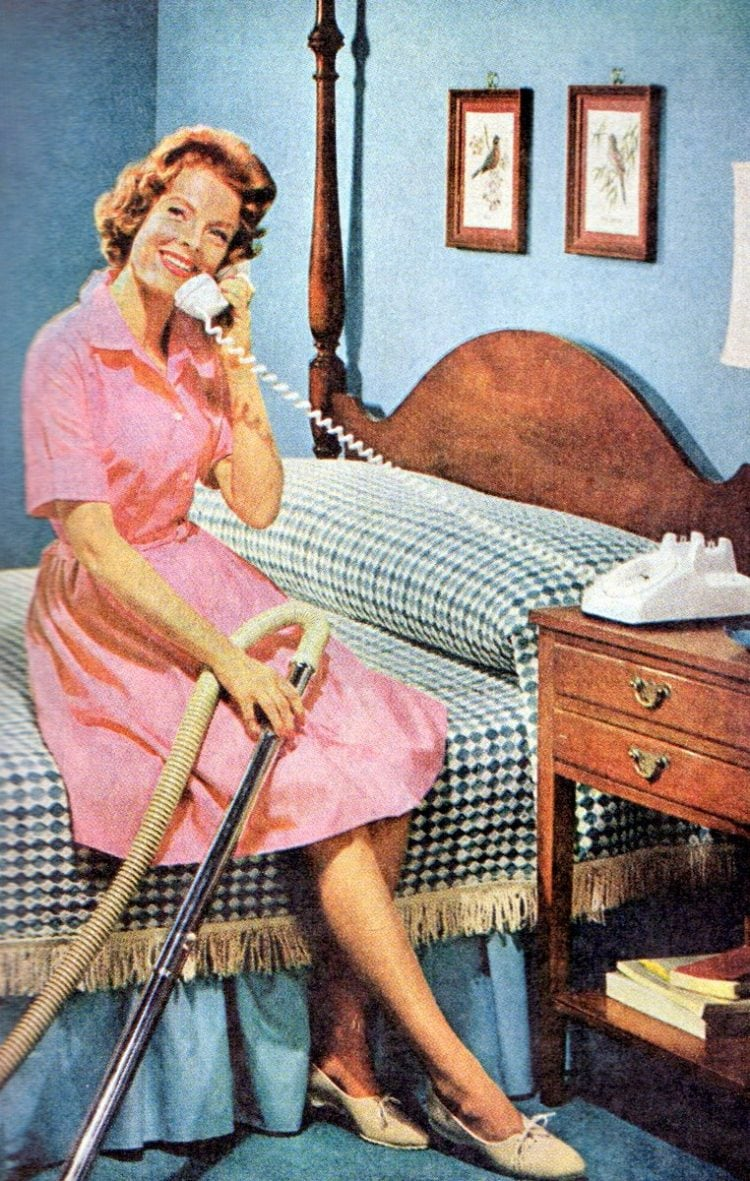 1959 - Housewife taking a break from cleaning for a phone call