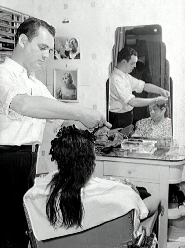 A man (presumably Francois) rolling this woman's hair in curlers