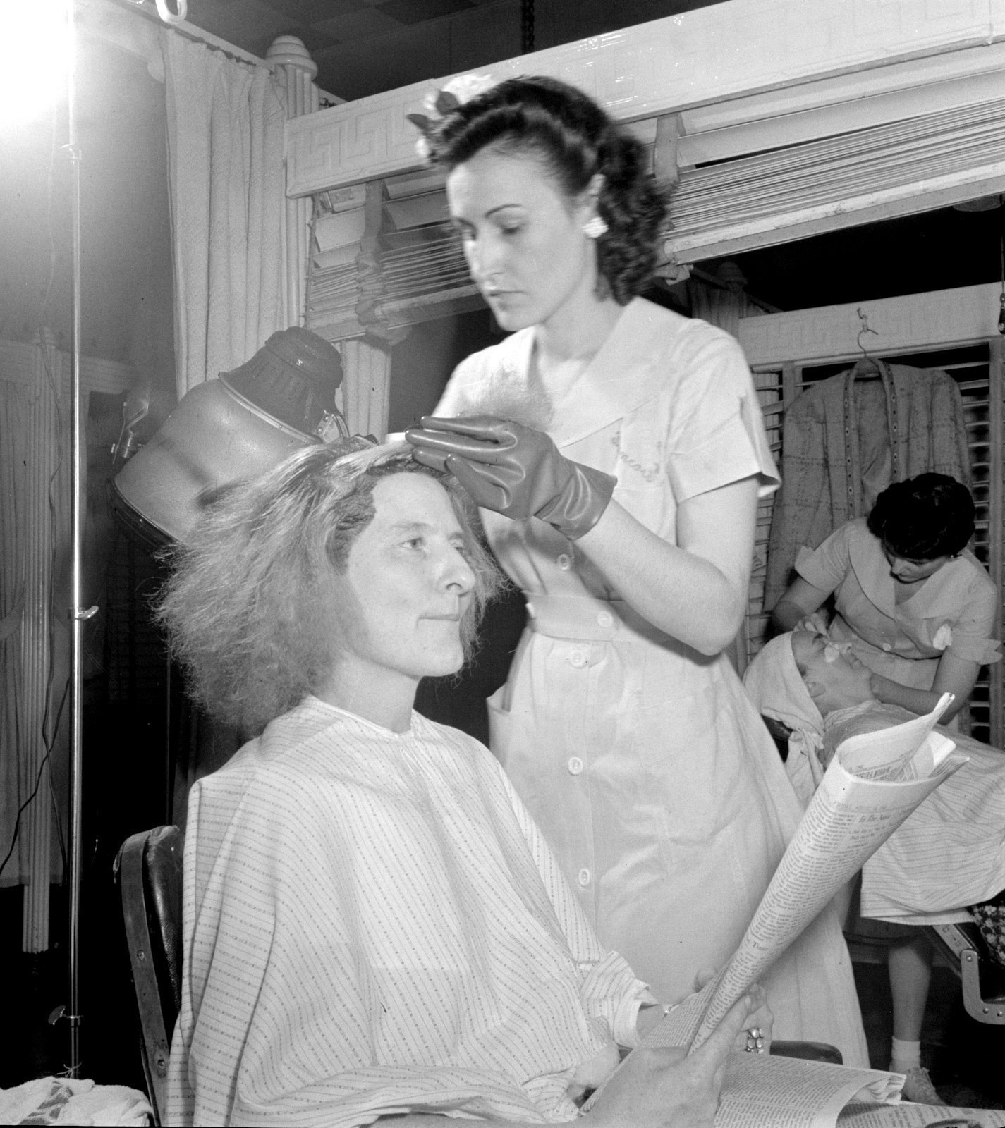 A salon professional highlights a woman's hair in the 1940s