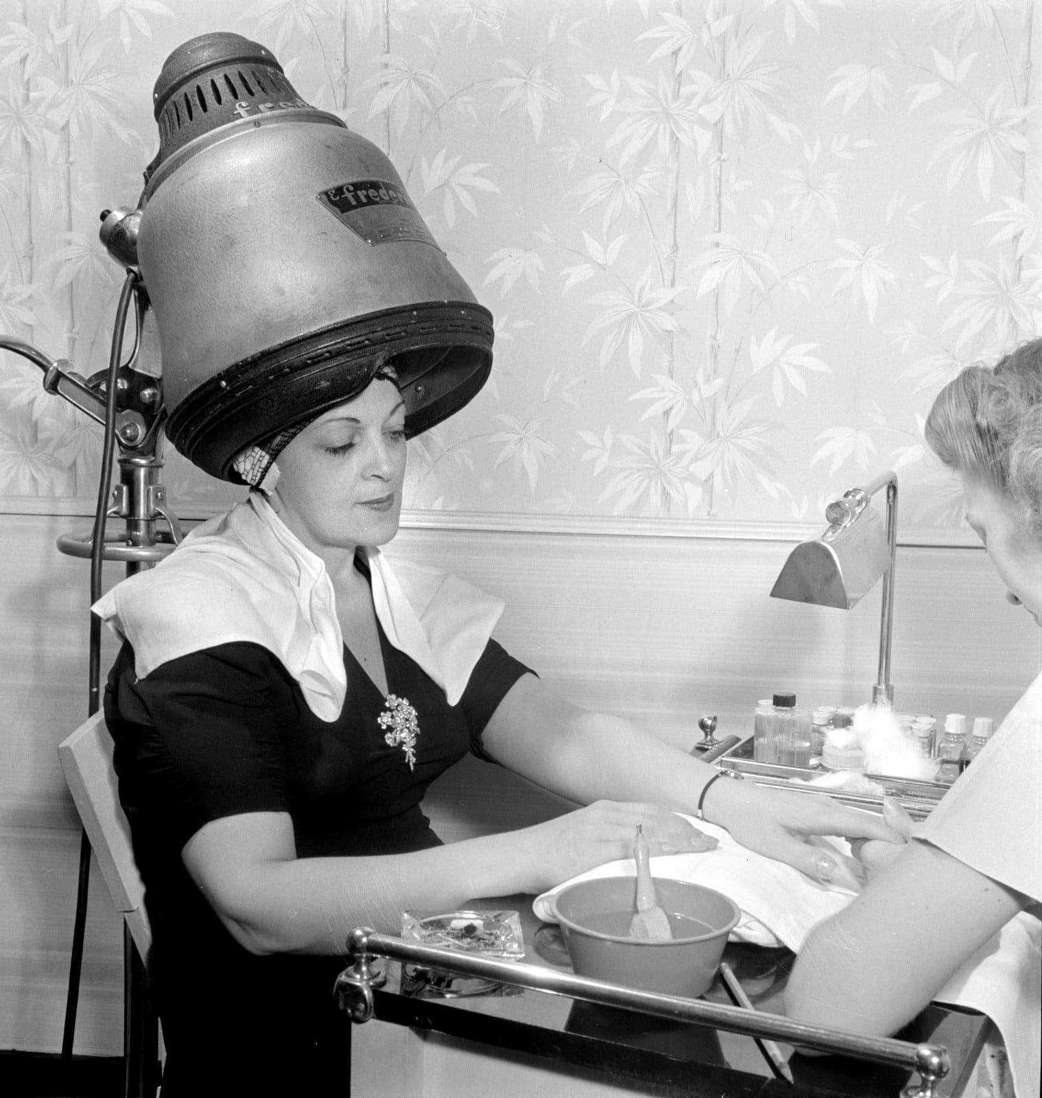A woman getting a manicure while she sits under a hairdryer