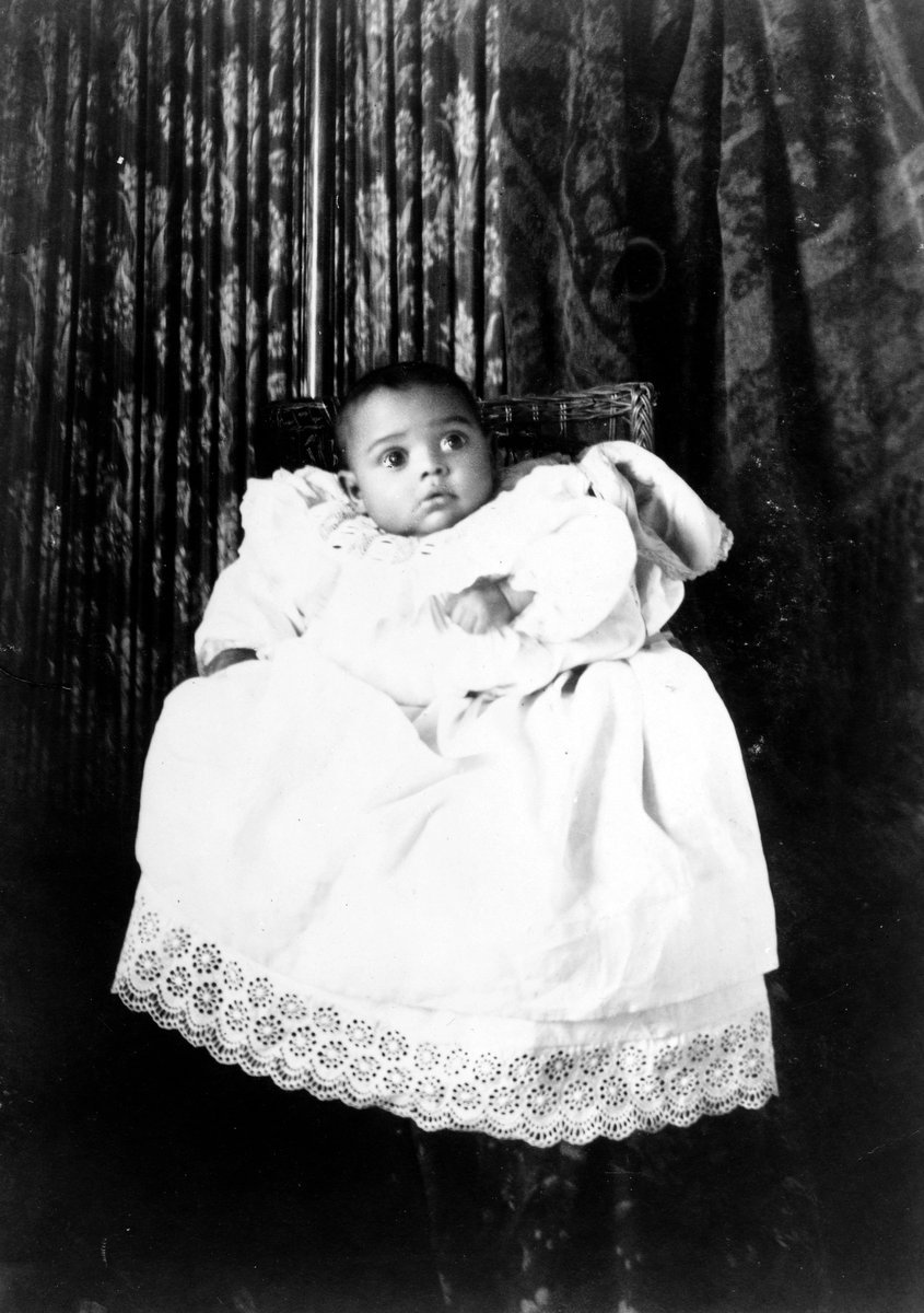 African American baby in a christening gown, from the WEB Du Bois collection (c1899)
