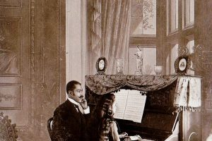 African American man giving piano lesson to young African American woman-c1899