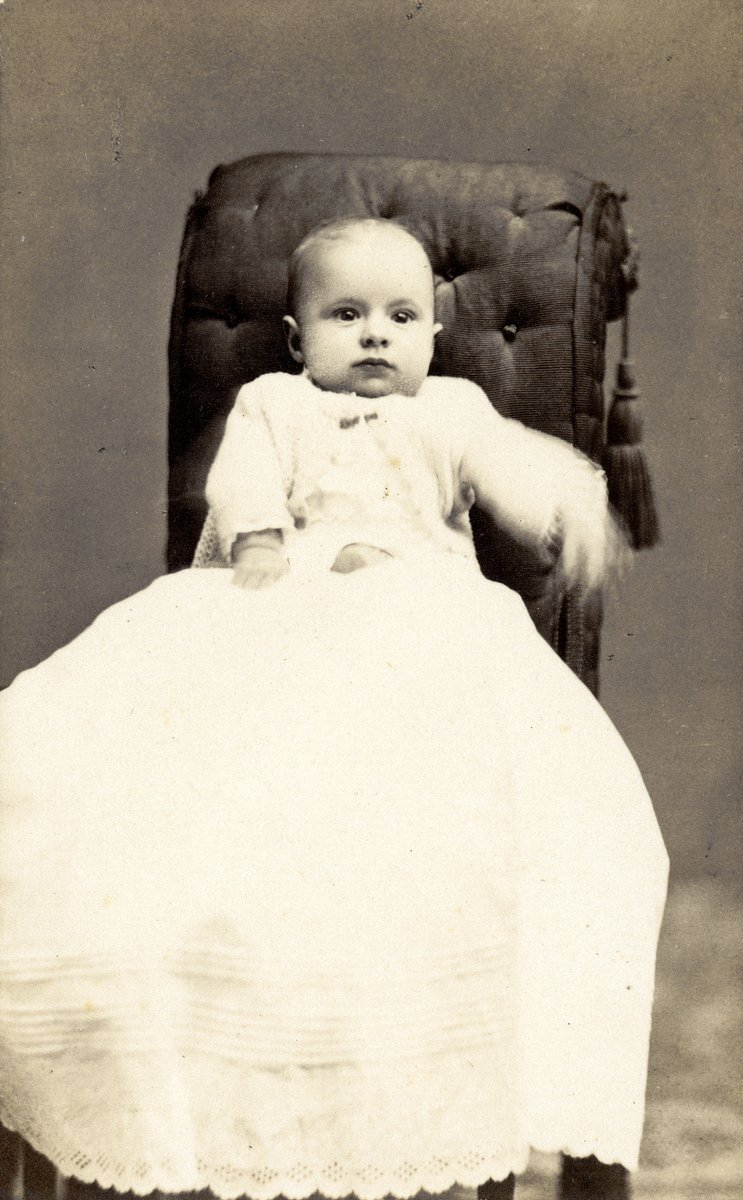 An intense little baby sitting for a portrait in Fitchburg, Mass (c1870s)