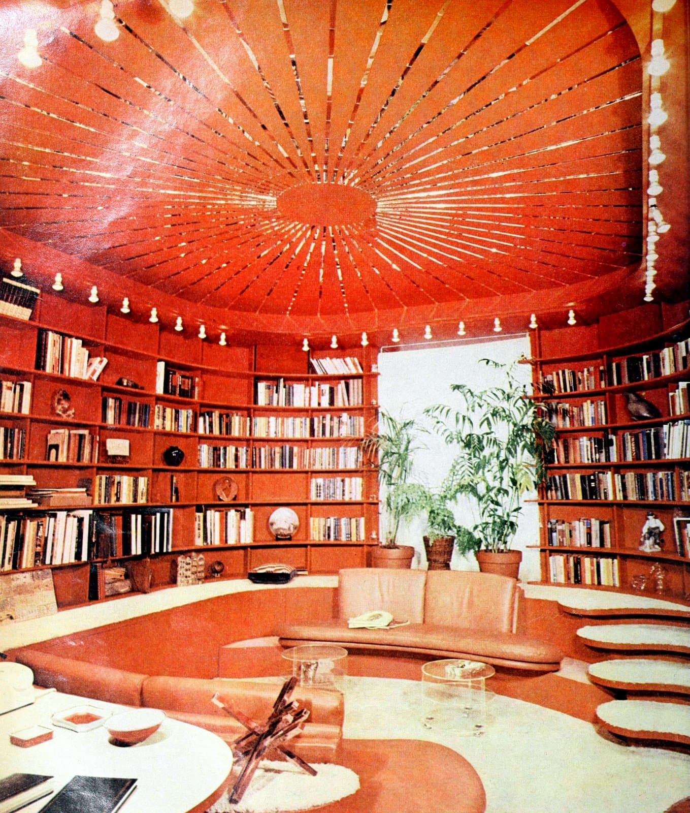 An orange oval library with built-in sunken seating area (1973)