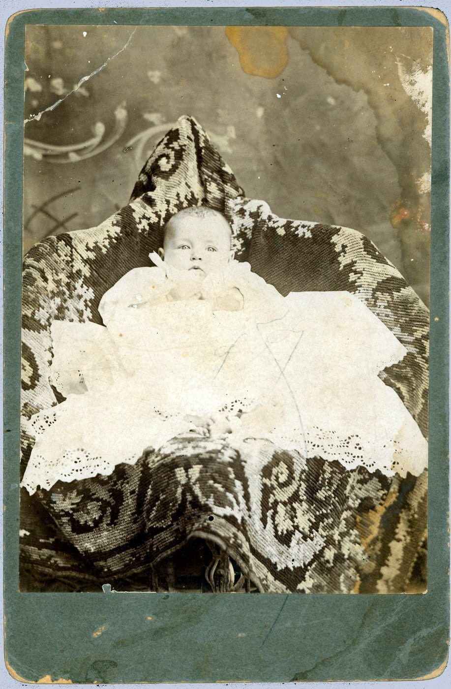 Antique baby portraits with a parent hiding under the cover
