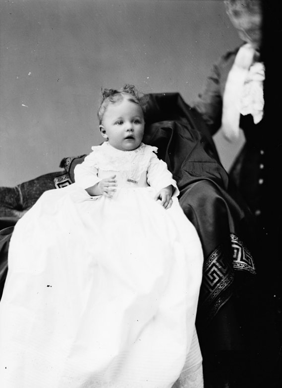 Antique photo of baby in christening gown with parent hiding behind (c1890s)