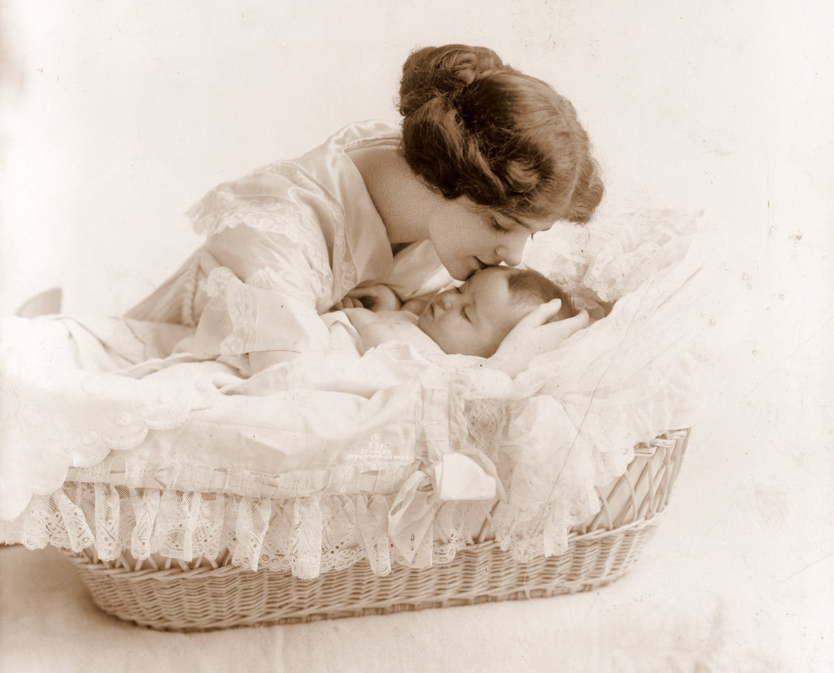 Antique portrait of mom kissing baby in a bassinet