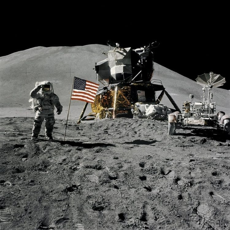 Astronaut saluting near American flag on moon