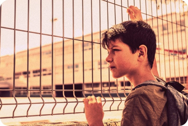Autistic boy looking at school through a fence