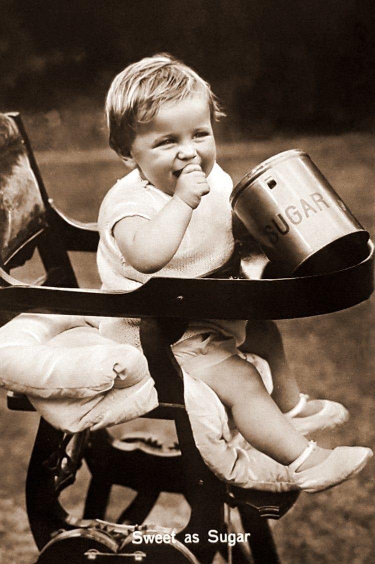 Baby in highchair with sugar jar