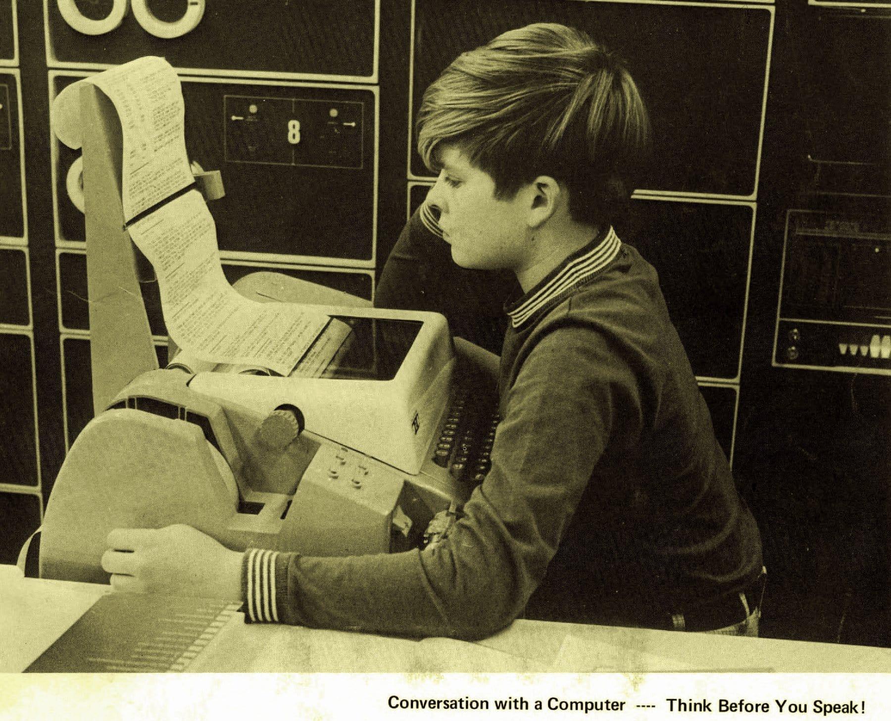 Boy reading computer printouts (1971)