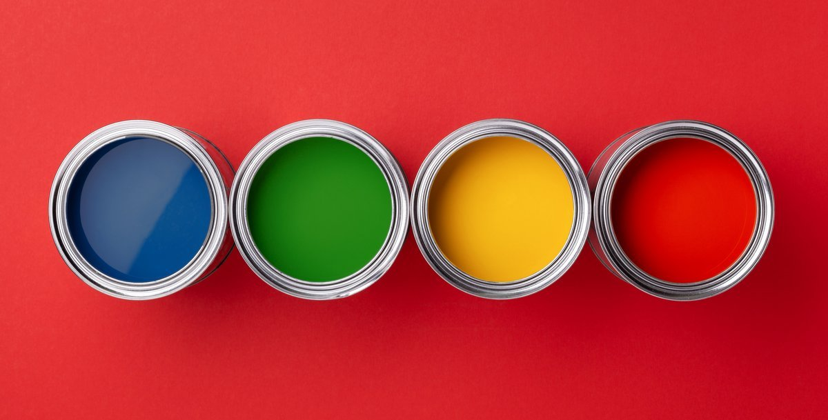 Cans of colorful paint on red background