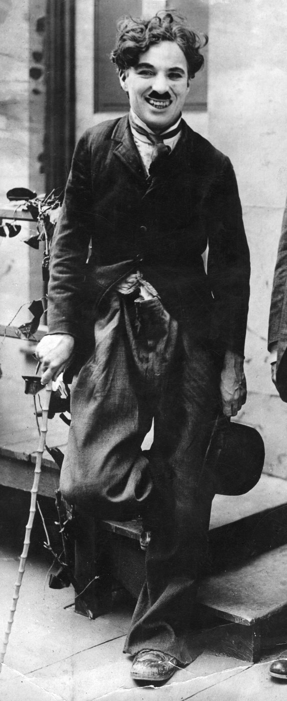 Charlie Chaplin standing and smiling