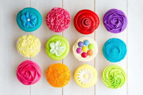 Colorful frosted cupcakes against a white background