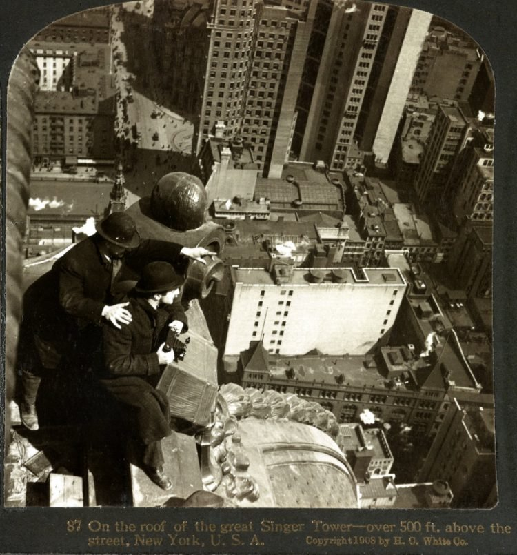 On the roof of the great Singer Tower--over 500 ft. above the street, New York - One man is holding a camera