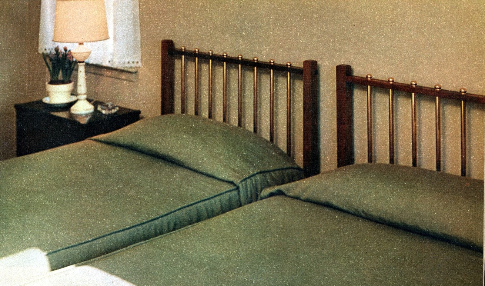 DIY bed headboard with shiny brass curtain rods (1956)