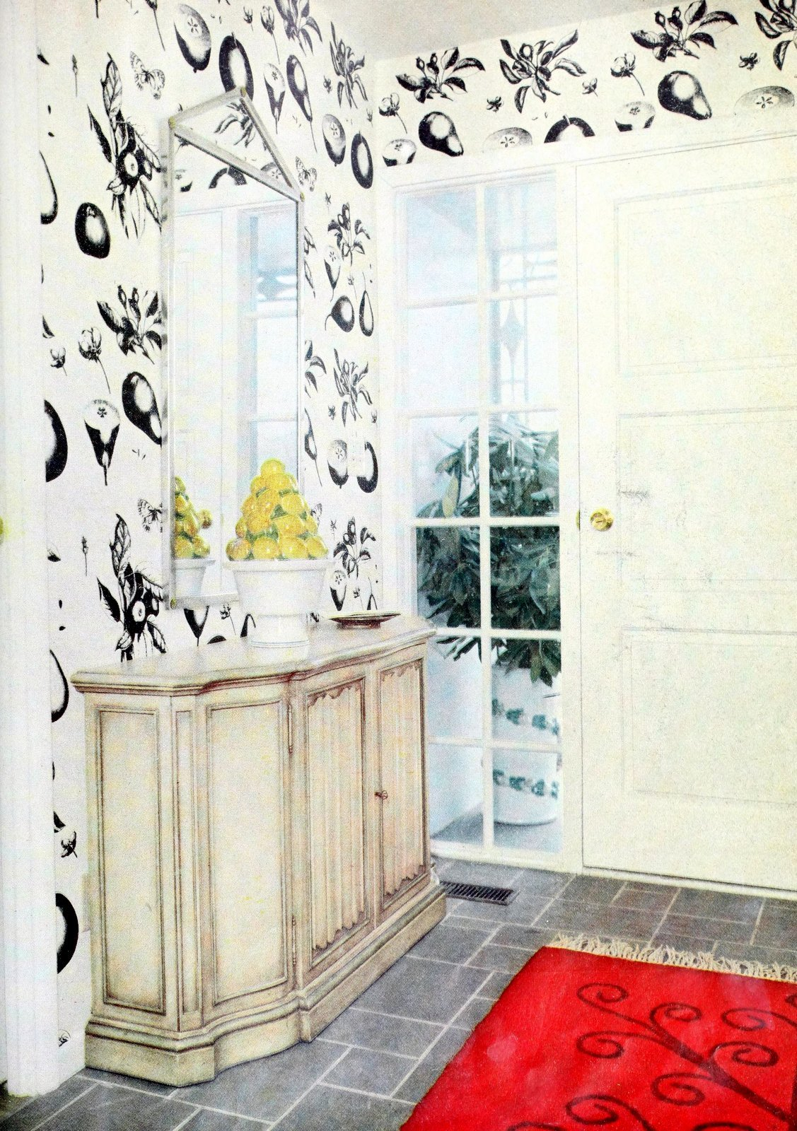 Entryway with red accent rug and funky black and white wallpaper (1958)