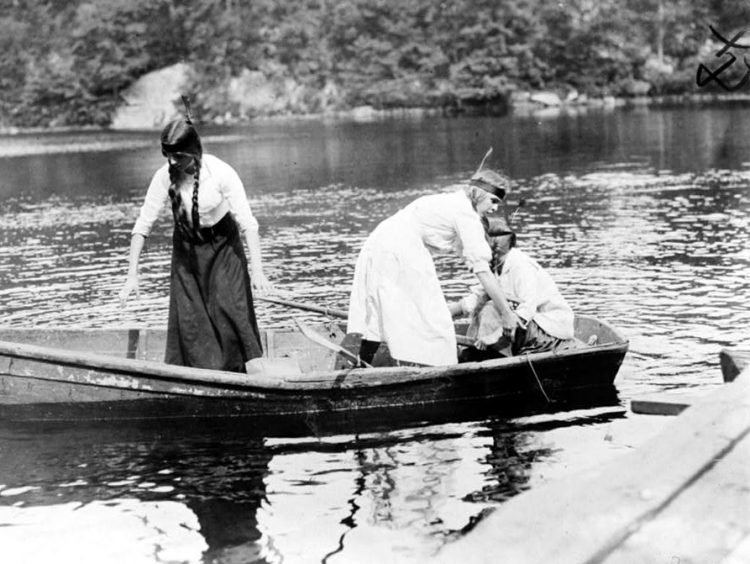 Girl Scouts in a boat at camp around 1912