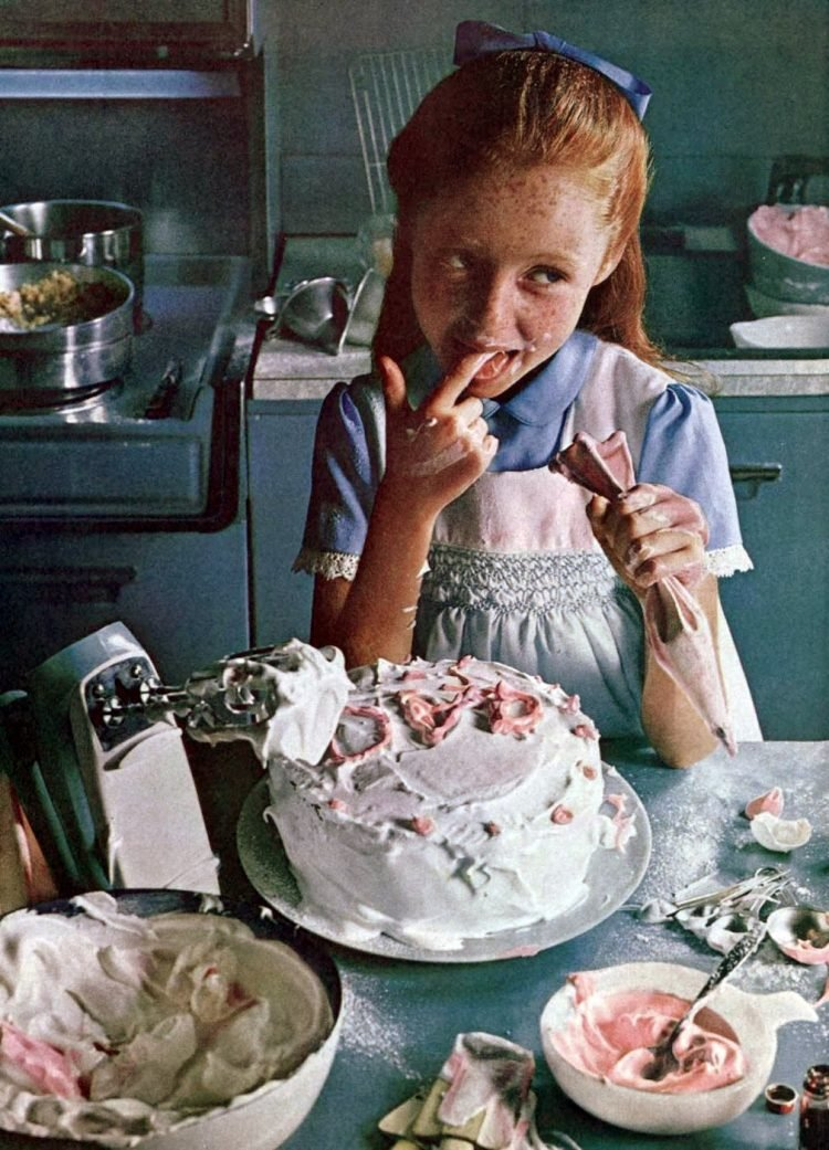 Girl frosting a cake in 1964