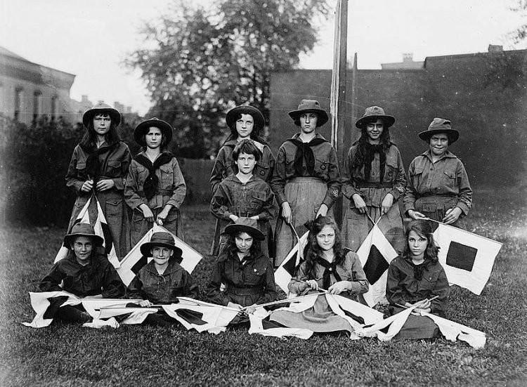 Girl scouts group holding semaphore flags