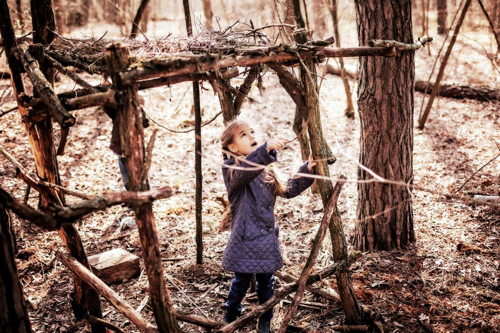 Girl starting to build a tree fort in a forested area