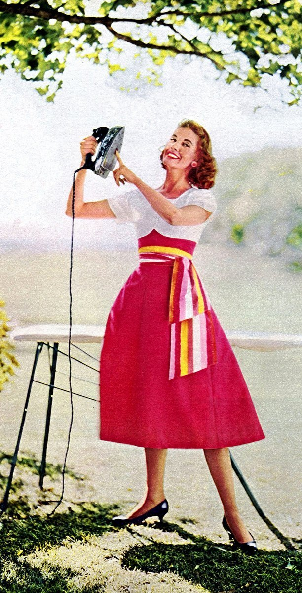 Happy 50s housewife with an iron outside