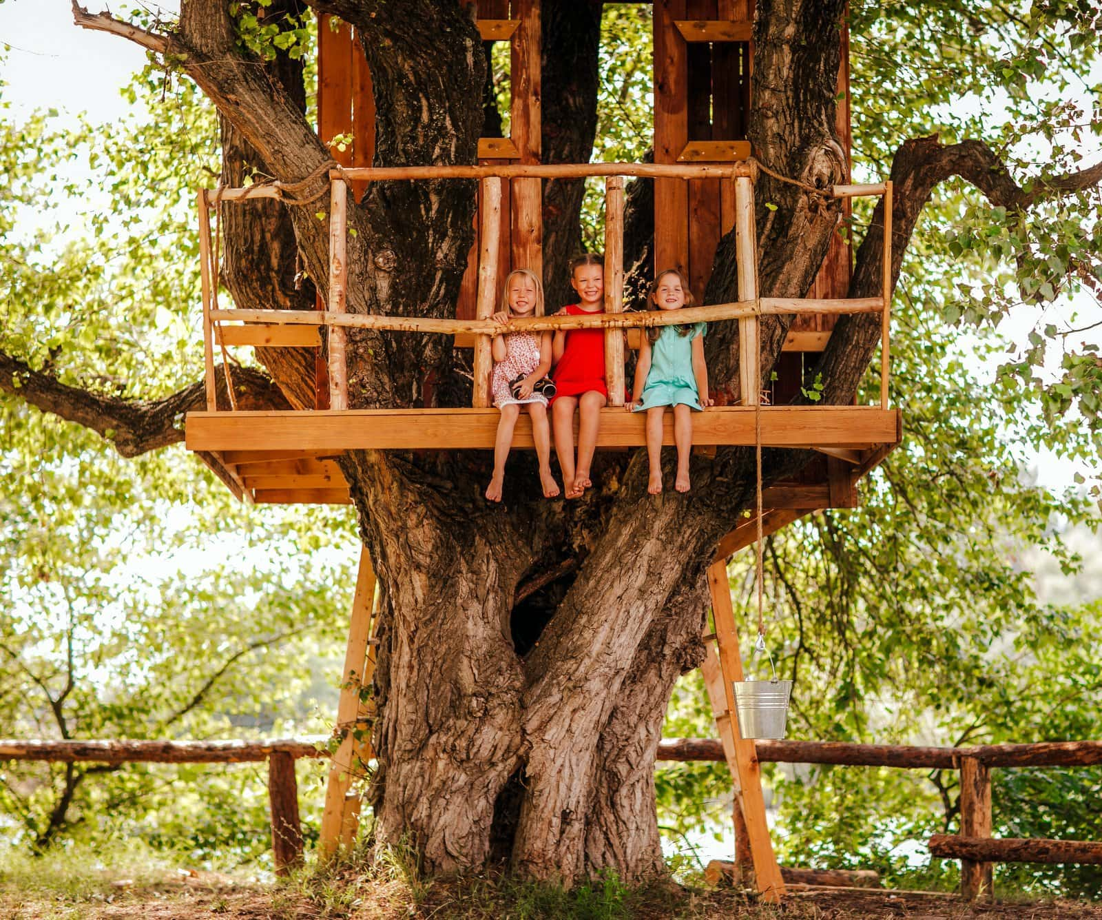 Kids sitting in a solid backyard treehouse