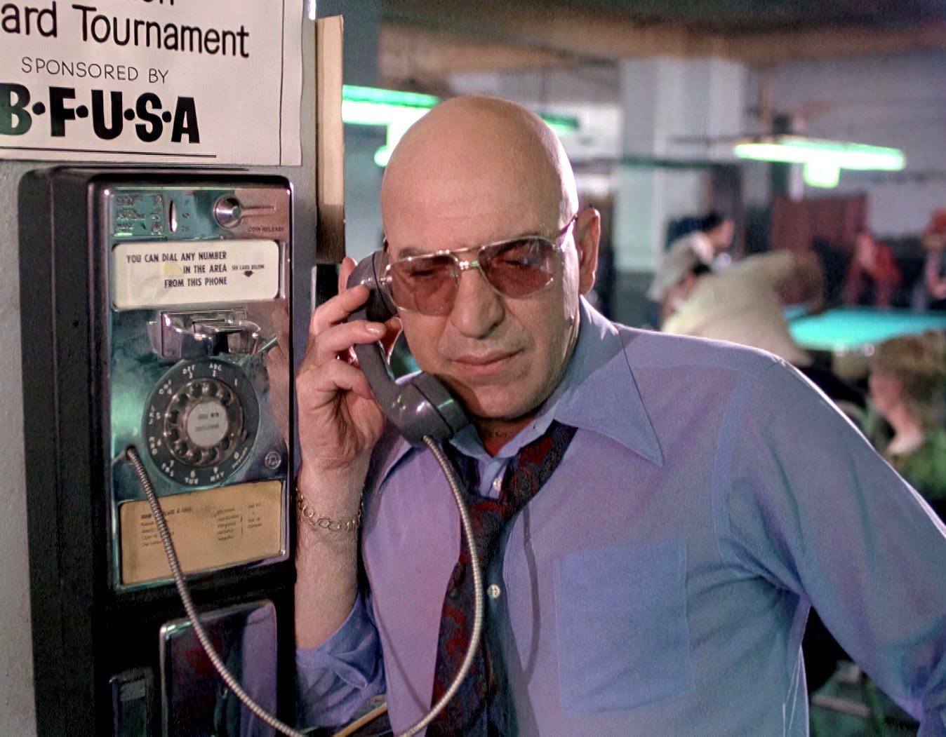 Kojak on vintage pay phone with rotary dial