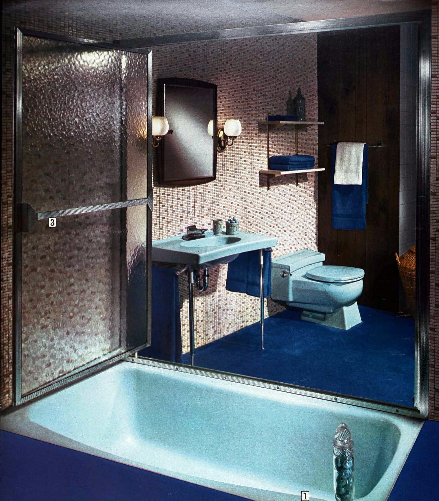 Light blue vintage bath fixtures with mosaic tile walls and dark blue carpet (1966)
