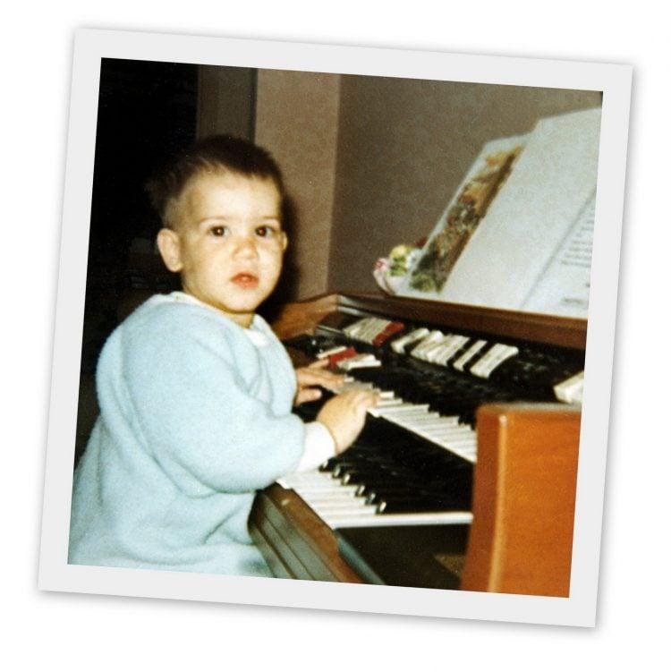 Little boy playing a vintage Wurlitzer home organ