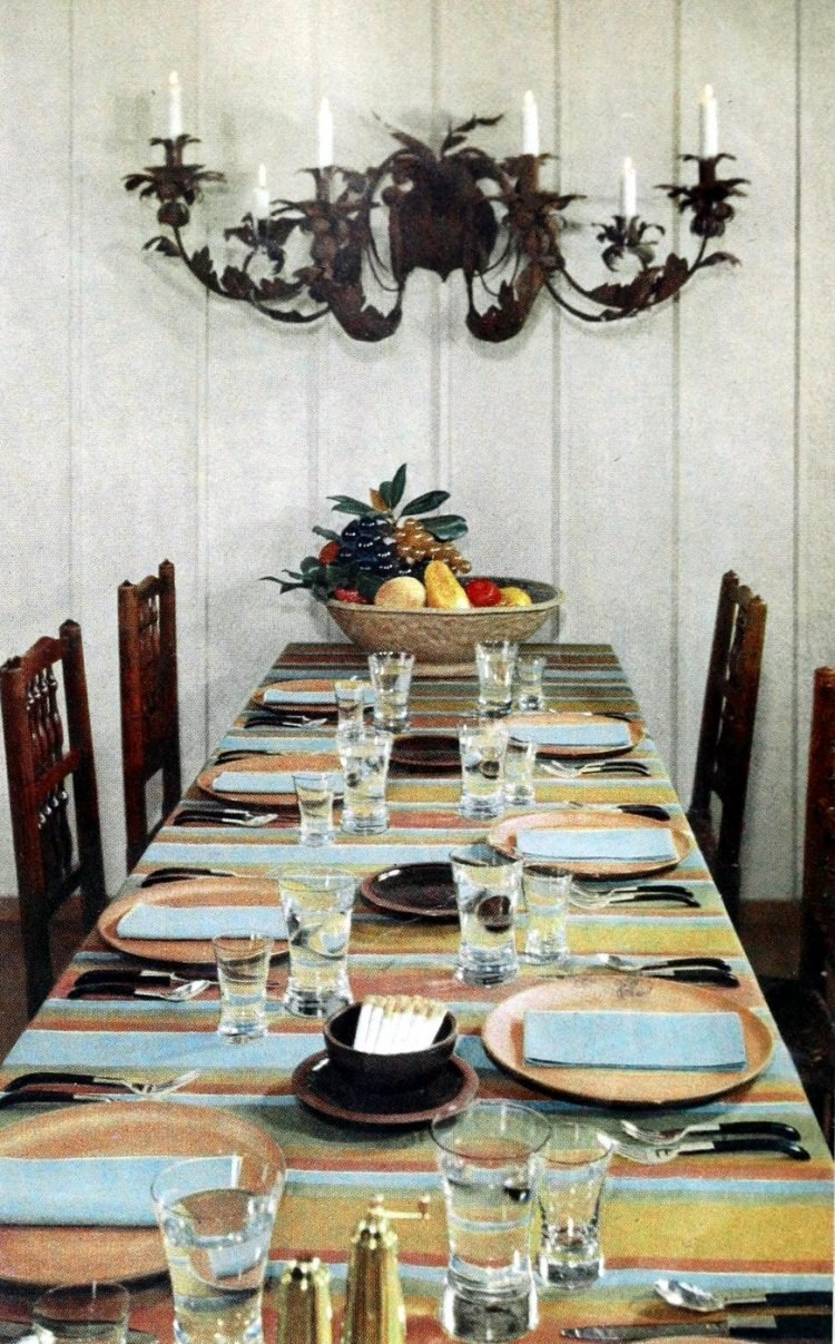 Long informal dining table with place settings in blue, orange and yellows
