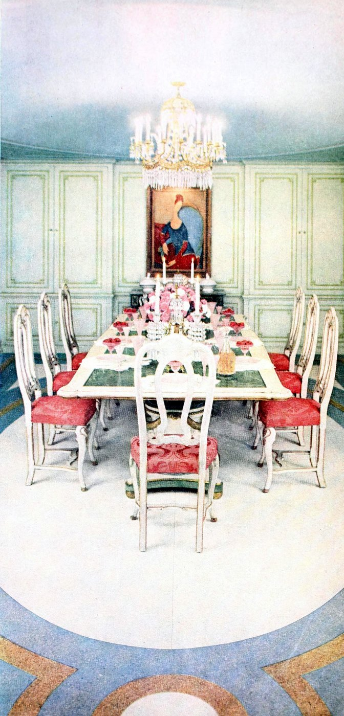 Long table with salmon-colored highlights for a dinner party in a classical formal dining room - 1950s