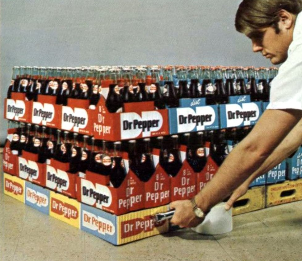 Man building a Dr Pepper merchandise display in 1970
