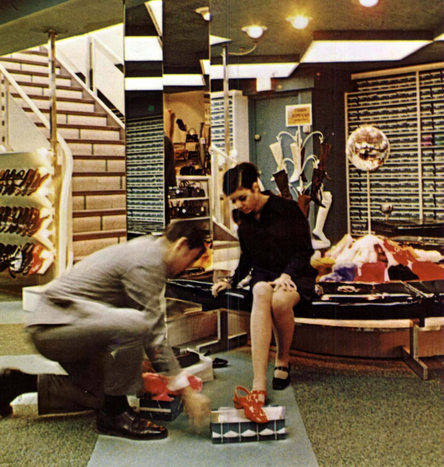 Man helping a young woman try on new shoes (1967)