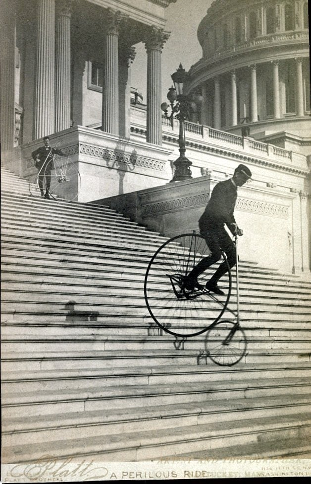 Man riding an antique bicycle down the stairs
