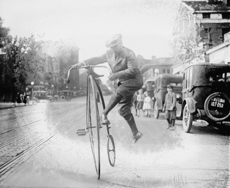 Man running to get on a vintage high wheel bicycle