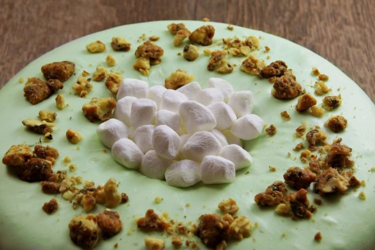 Marshmallows and nuts on top of Watergate cake