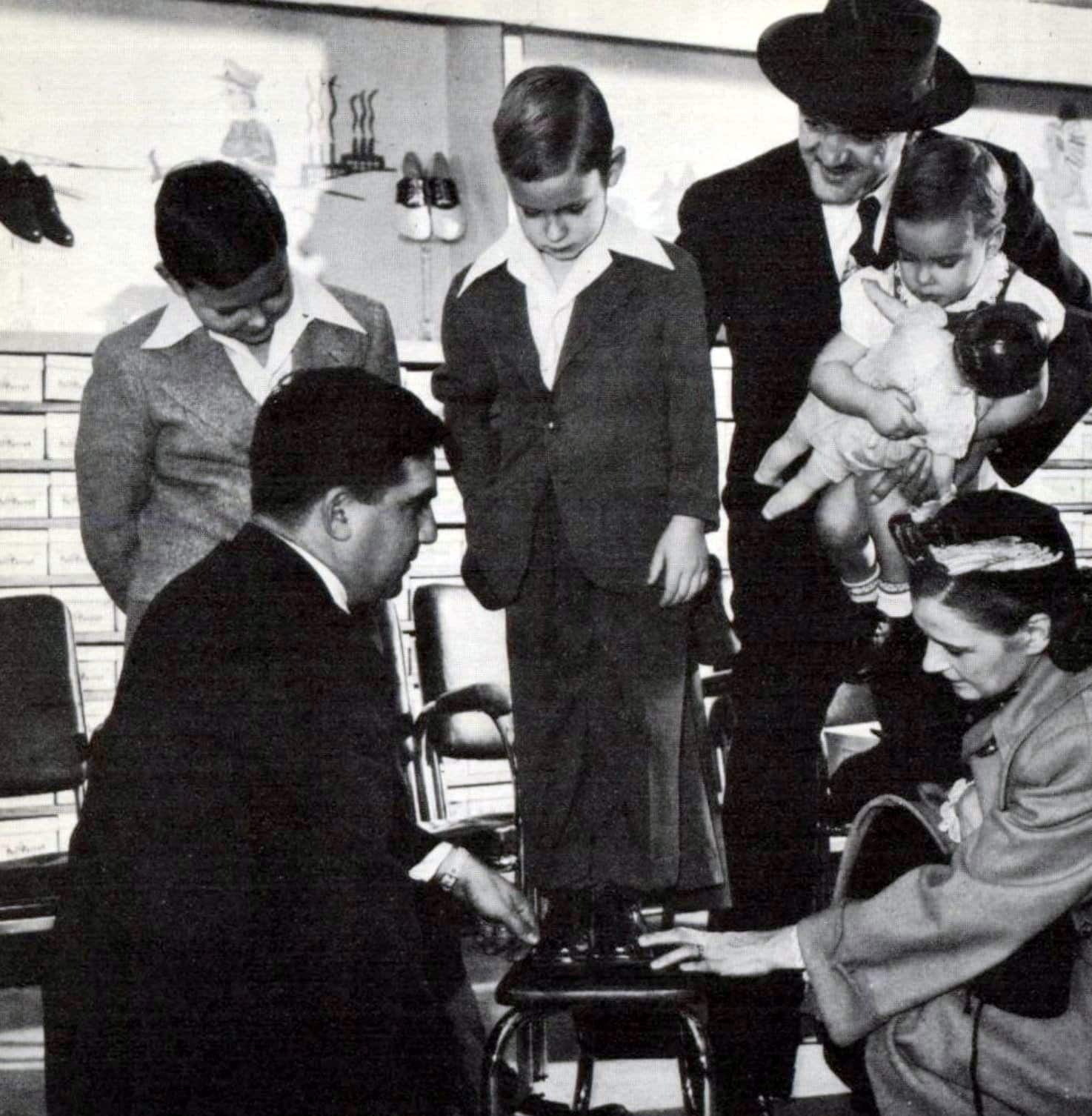 Measuring a boy's feet for a shoe fitting (1949)