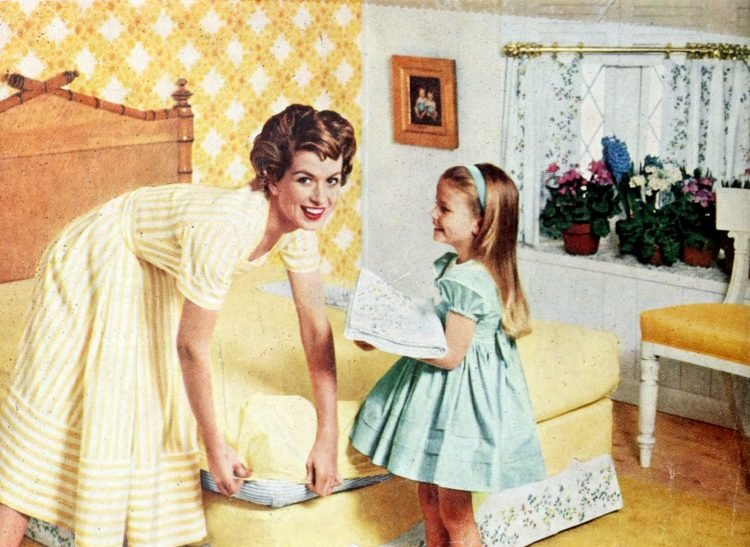 Mother and daughter changing yellow bed sheets in vintage 50s master bedroom
