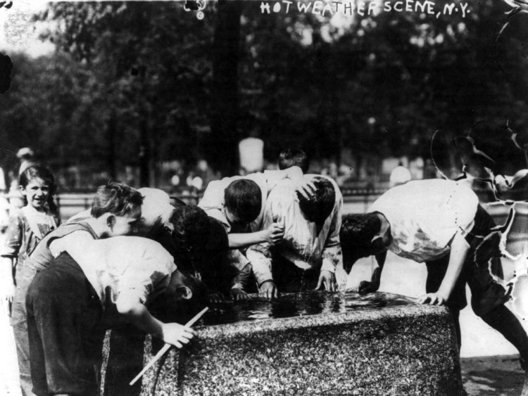 NYC hot weather street scene - boys dipping their heads in fountain
