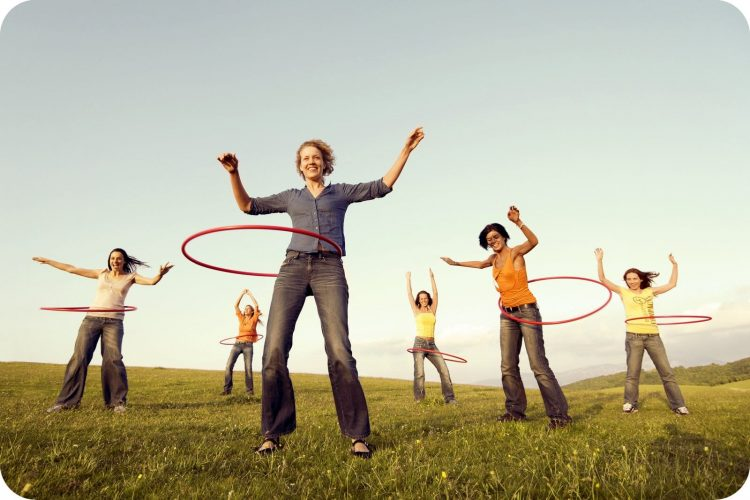 People out hula hooping in a field