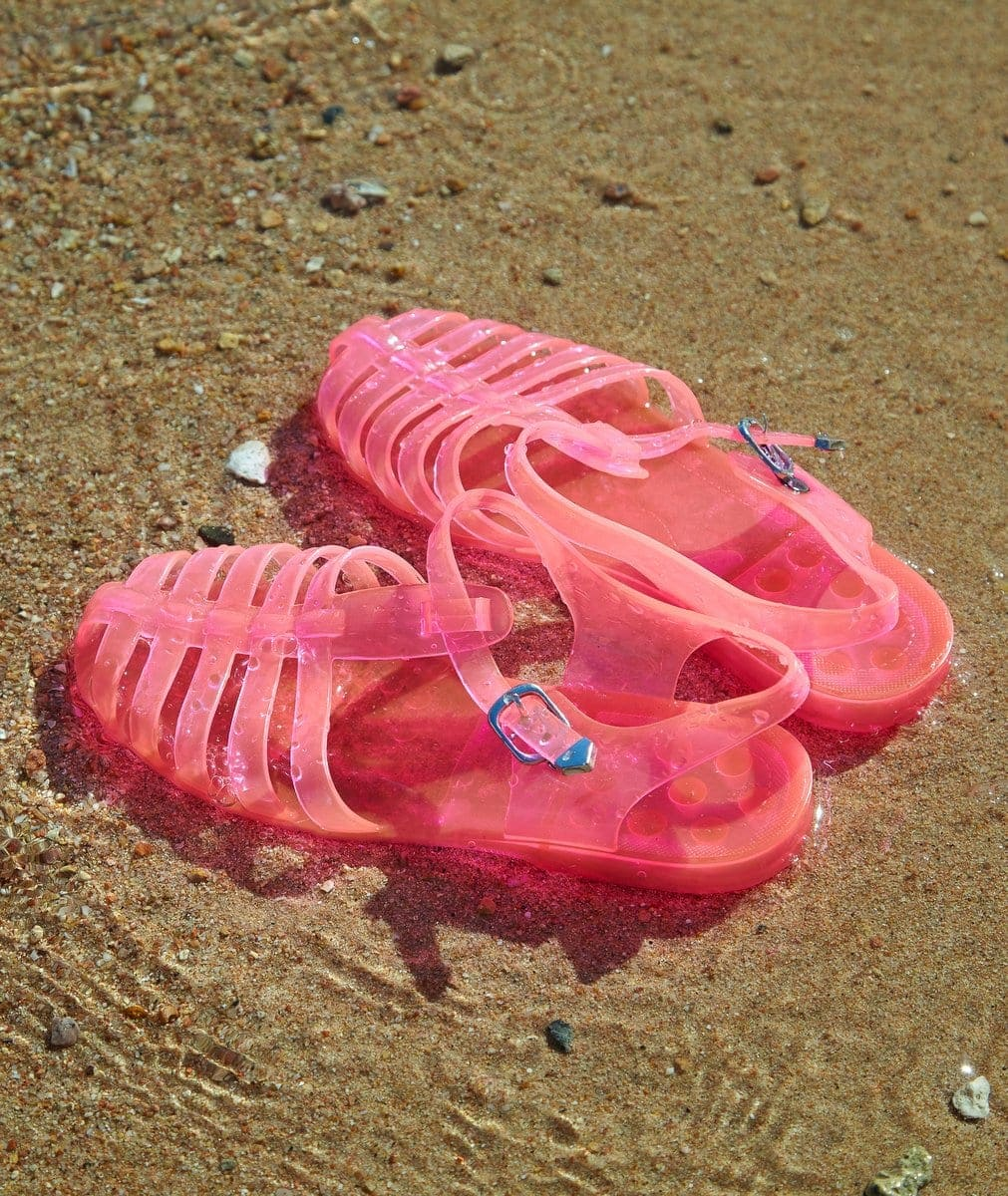 Pink jelly shoes on the beach