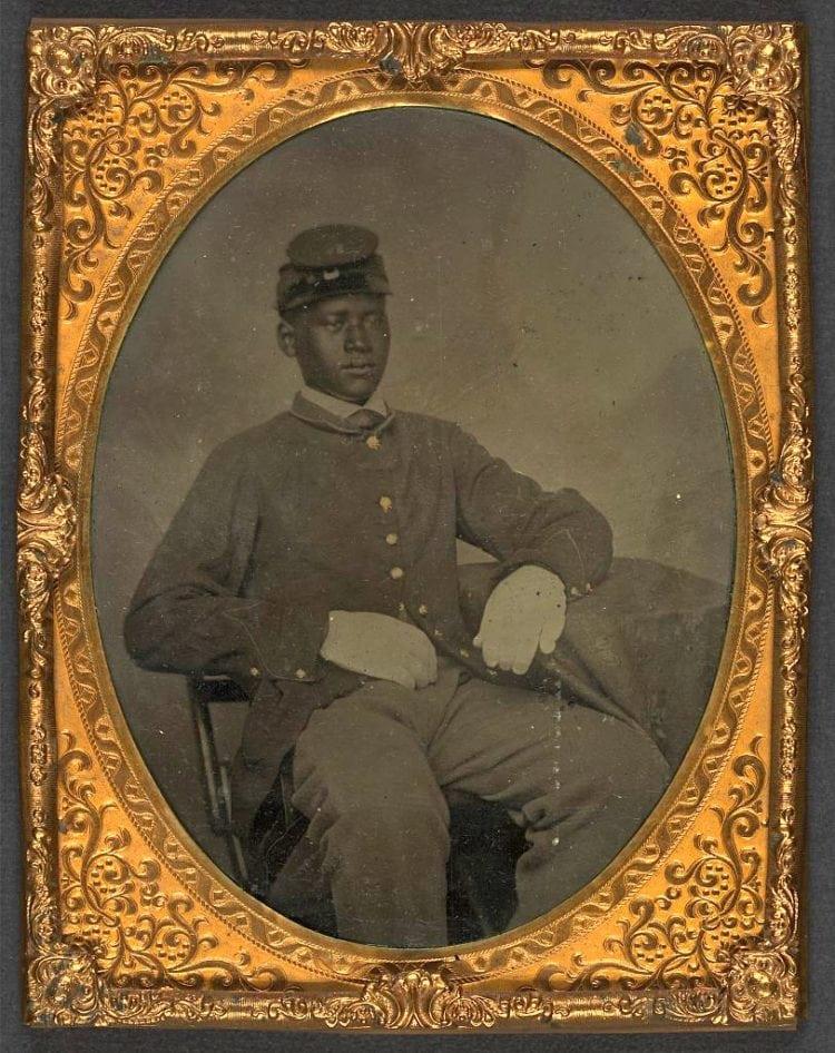 Seated black soldier, frock coat, gloves, kepi
