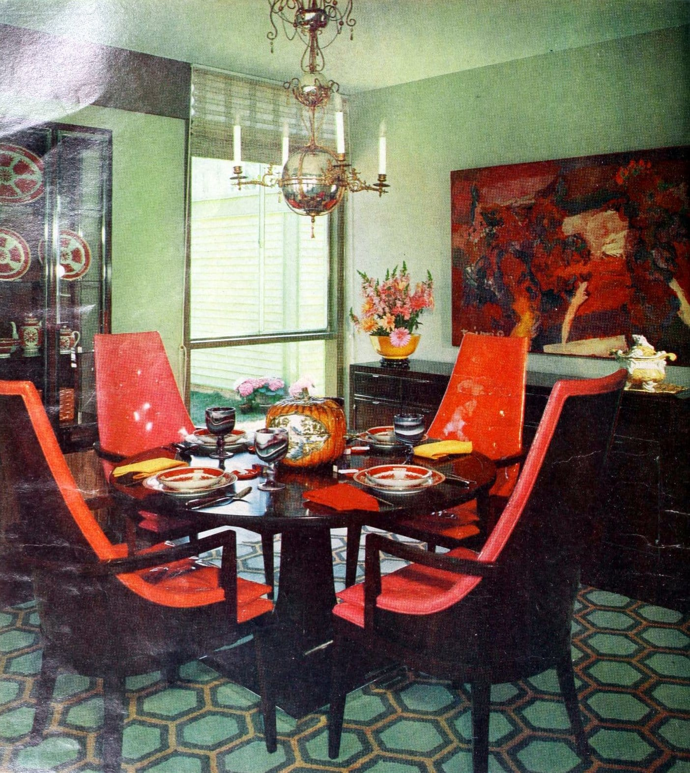 Shiny red vintage patent leather chairs around a circular dining table (1965)