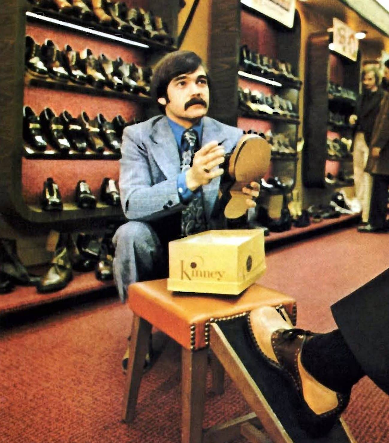 Shoe store salesman helping a customer try on shoes (1973)