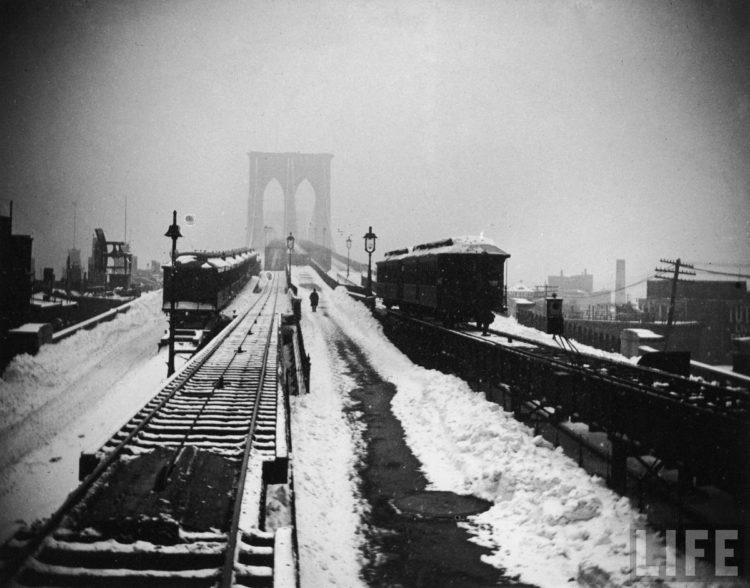 Snow-covered train tracks, rooftops and arches of the Brooklyn Bridge seen from the rear of a train during the Blizzard of 1888