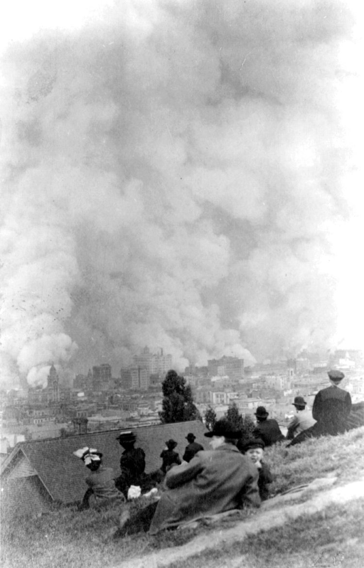 Spectators sitting on hillside watching fires consume the city after the 1906 San Francisco earthquake