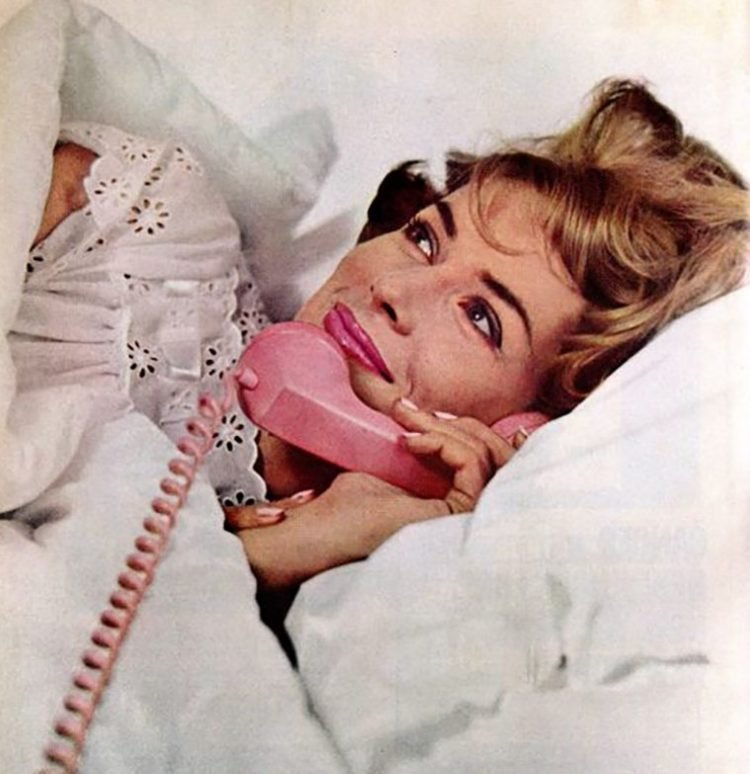 Taking a call in bed - pink telephone 1950s